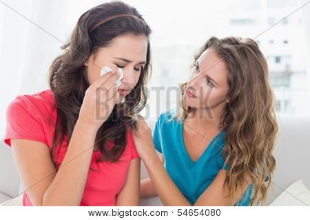 Young woman consoling a crying female friend while sitting on sofa at home