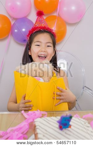 Close-up portrait of a cheerful surprised little girl at her birthday party