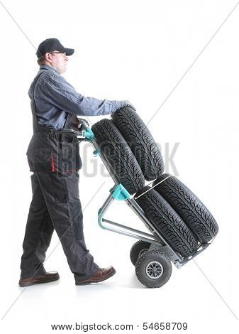 Serviceman carrying a set of four new car tires using hand truck shot on white