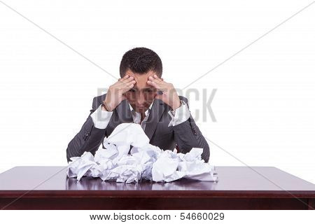 Tensed young businessman with crumpled papers on his desk