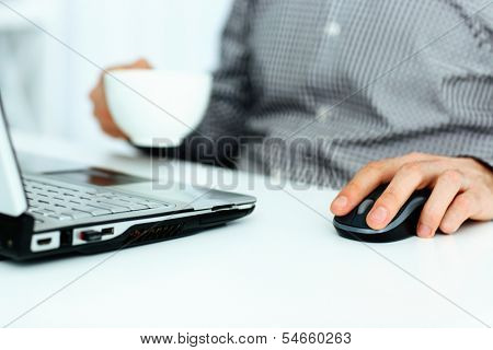 Close-up portait of male hands on mouse and holding cup of coffee