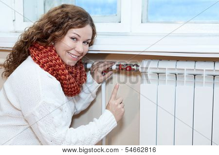 Happy Woman Gesturing When Controling Thermostat On Central Heating Radiator