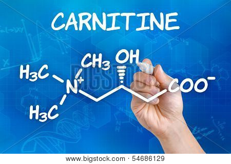 Hand with pen drawing the chemical formula of carnitine