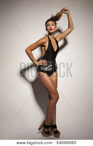 Seductive young woman with her brunette hair in a ponytail in black lingerie posing in high heels with her leg raised giving the camera a sultry provocative look