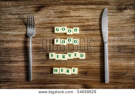 Silverware On Table And Good Food Served Here Sign
