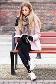 stock photo of overcoats  - Gorgeous blonde reading a book in the street - JPG