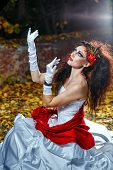 stock photo of carnal  - Attractive bride in a wedding dress with bright makeup red shawl - JPG