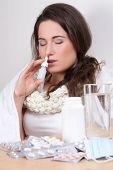 stock photo of snot  - young attractive woman using nasal spray in her living room - JPG
