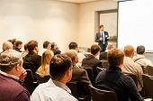 stock photo of seminars  - people sitting at the business conference and speaker at the screen - JPG