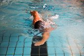 pic of crawling  - Man swims forward crawl style in public swimming pool - JPG