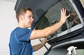 stock photo of car-window  - Car wrappers tinting a vehicle window with a tinted foil or film using heat gun and squeegee - JPG
