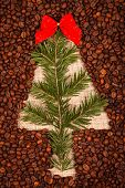 stock photo of juniper-tree  - Symbol of Christmas tree with red ribbon and juniper leaves on burlap made of coffee beans - JPG