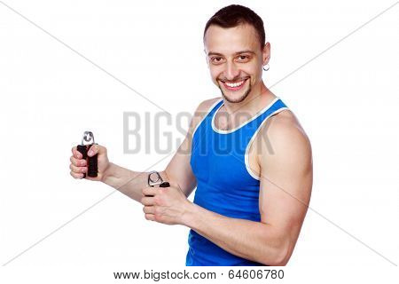 Smiling muscular sportsman with expanders over white background