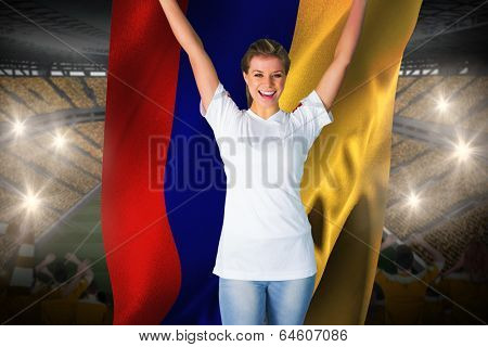 Pretty football fan in white cheering holding colombia flag against vast football stadium with fans in yellow