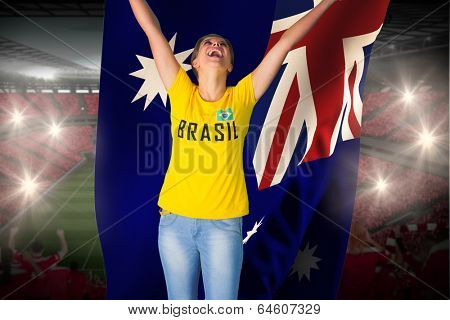 Excited football fan in brasil tshirt holding australia flag against vast football stadium with fans in red