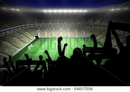 Silhouettes of football supporters against large football stadium with lights