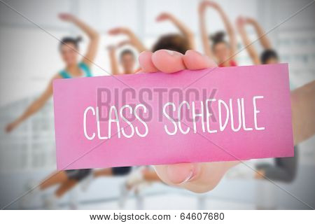 Woman holding pink card saying class schedule against fitness class in gym