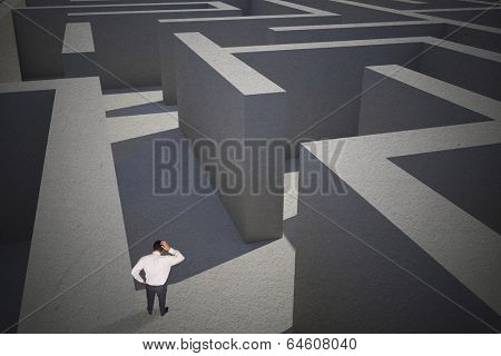 Thinking businessman scratching head against difficult maze puzzle