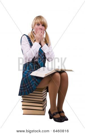 Schoolgirl Is Sitting On The Stack Of Book And Watch Furtively Textbook.