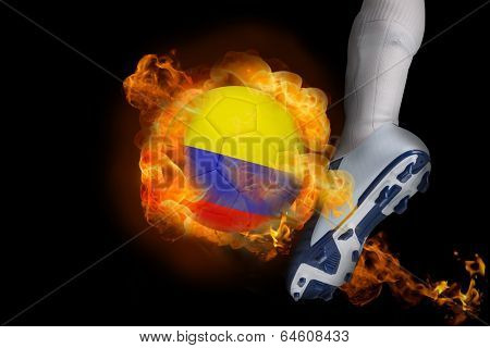 Football player kicking flaming colombia ball against black