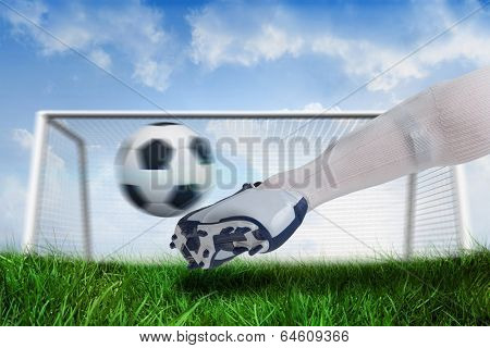 Composite image of close up of football player kicking ball against goalpost on grass under blue sky