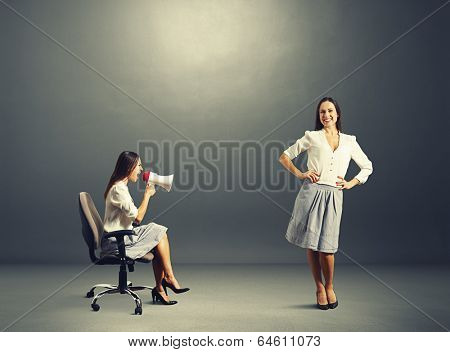 angry woman and smiley calm woman over dark background