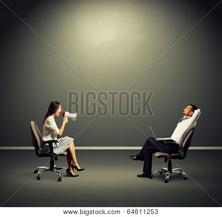 smiley man listening angry woman over dark background