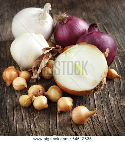 Different Varieties Of Onions On A Wooden Background