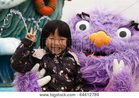 Young girl with plush animal standing and smiling.
