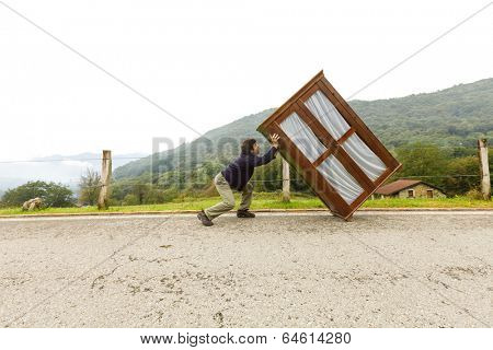 Man carries wardrobe along a mountain road