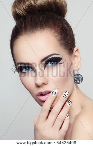 Portrait of young beautiful woman with stylish cat eye make-up and fancy polka dot manicure