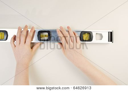 Hands Holding Level Against Interior Wall Of Home