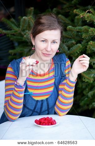 Beautiful Girl In Bright Clothes Eating Raspberry