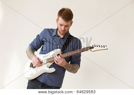 Handsome man playing on guitar