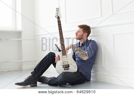 Handsome guy on the floor with electric guitar