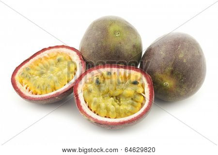 passion fruits and a cut one on a white background