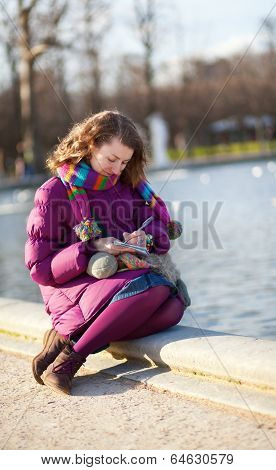 Beautiful Girl In Bright Clothes Writing Something In Her Notebook