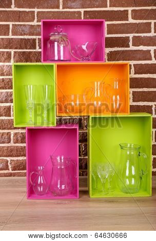 Beautiful colorful shelves with tableware  on  brown  wall background