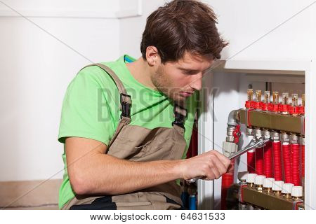 Repairman Fixing Valves In Home