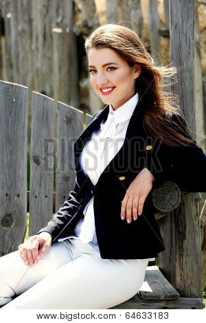 Elegant woman in costume for  horseback riding outdoors