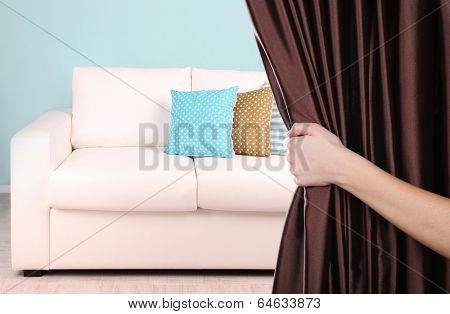 Hand opening curtain on room background