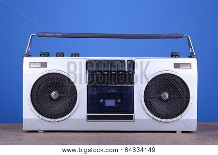 Retro cassette stereo recorder on table on blue background