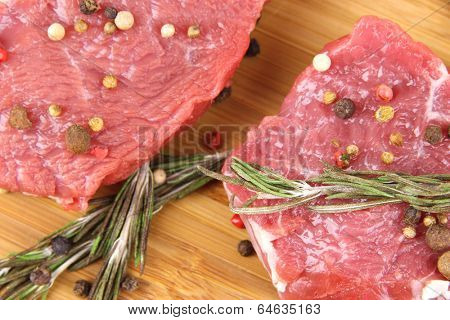 Raw beef meat with spices on wooden background