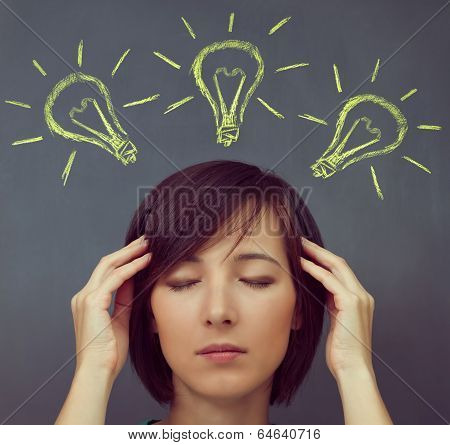 Woman Touches Her Head On A Background Of Light Bulbs