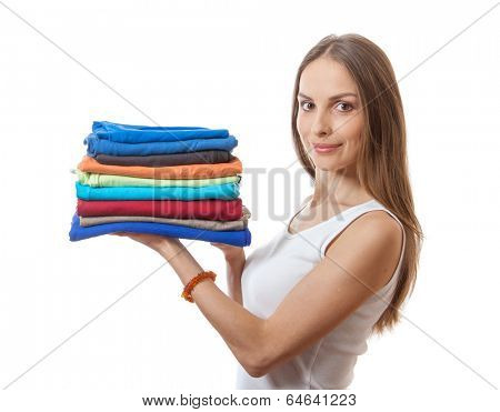 young woman holding a pile of clothes, isolated on white background