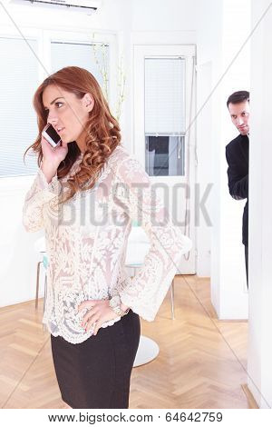 Suspicious Man Looking At His Woman While She Talking On The Phone