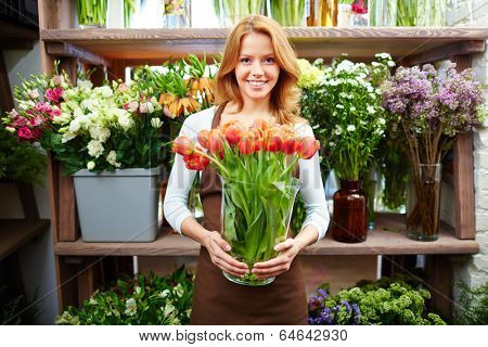 Portrait of happy female florist with big vase of red tulips looking at camera