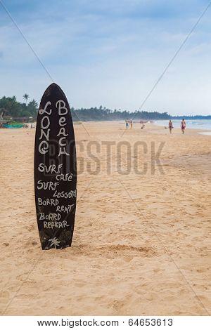 HIKKADUWA, SRI LANKA - FEBRUARY 20, 2014: Surf board on sandy Weligama beach, a well-known international destination for board-surfing.