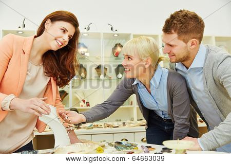 Smiling saleswoman advising two custormers in a jewelry store