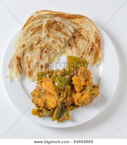 Aloo capsicum, potato and bell pepper vegetarian curry, served with paratha fried flatbread in the traditional way, viewed from above